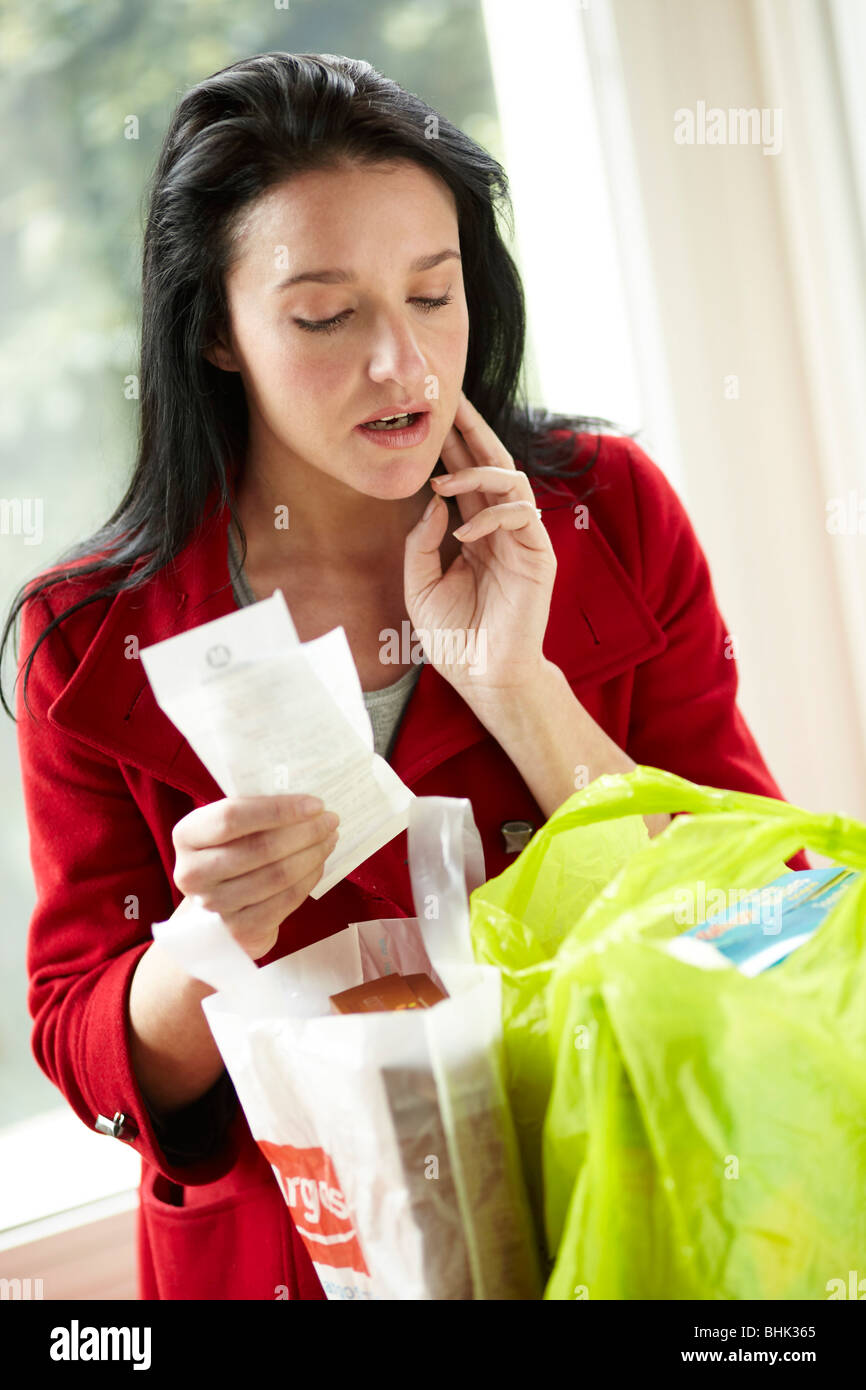Woman looking at receipt - Stock Image