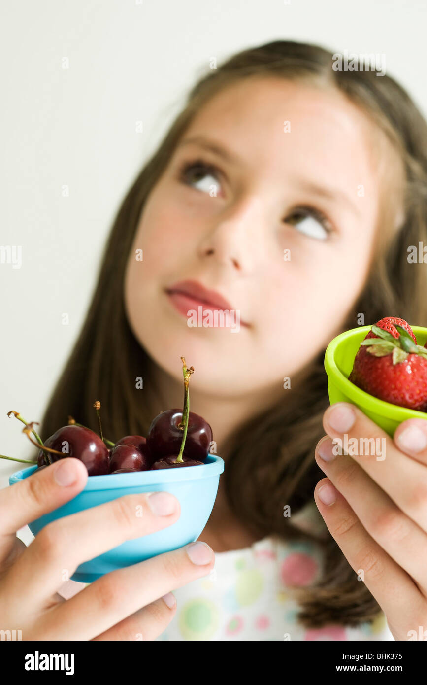 Girl deciding between bowl of cherries and bowl of strawberries - Stock Image