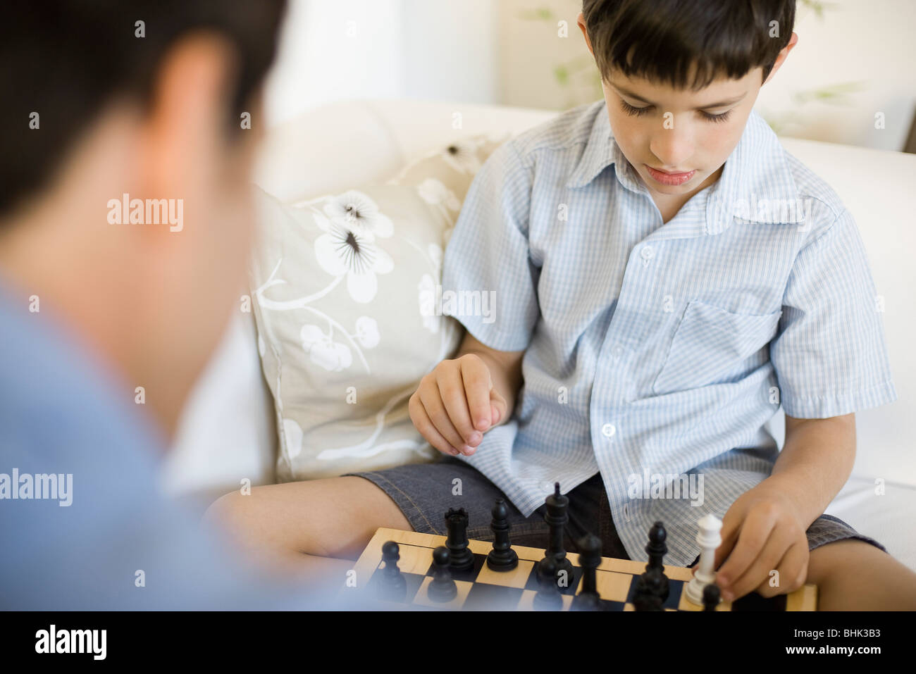 Boy playing chess with his father, cropped - Stock Image