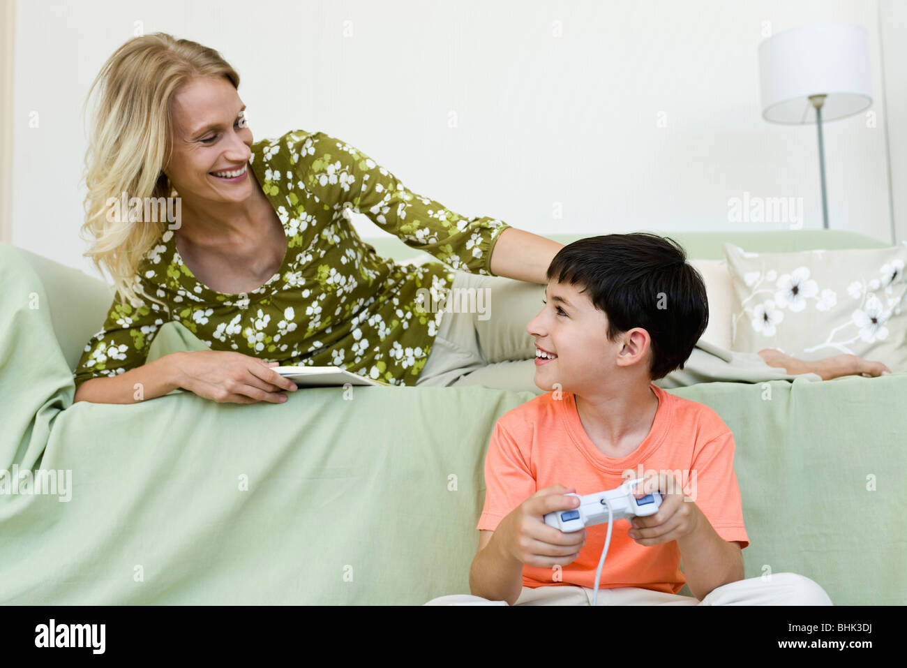 Young boy sitting on floor playing video game looking up at mother relaxing on sofa - Stock Image
