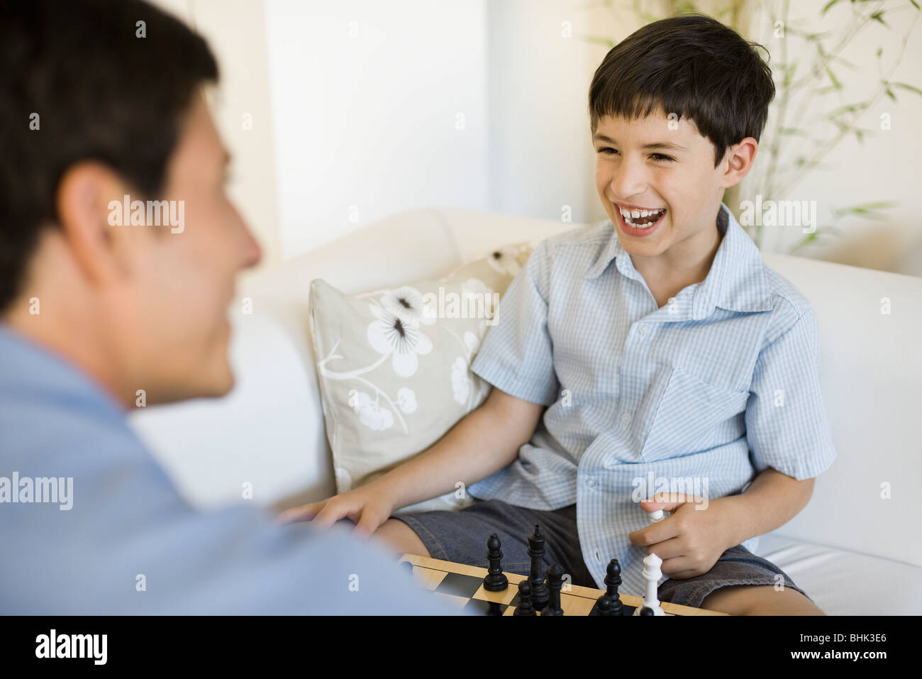Father and young son playing chess - Stock Image