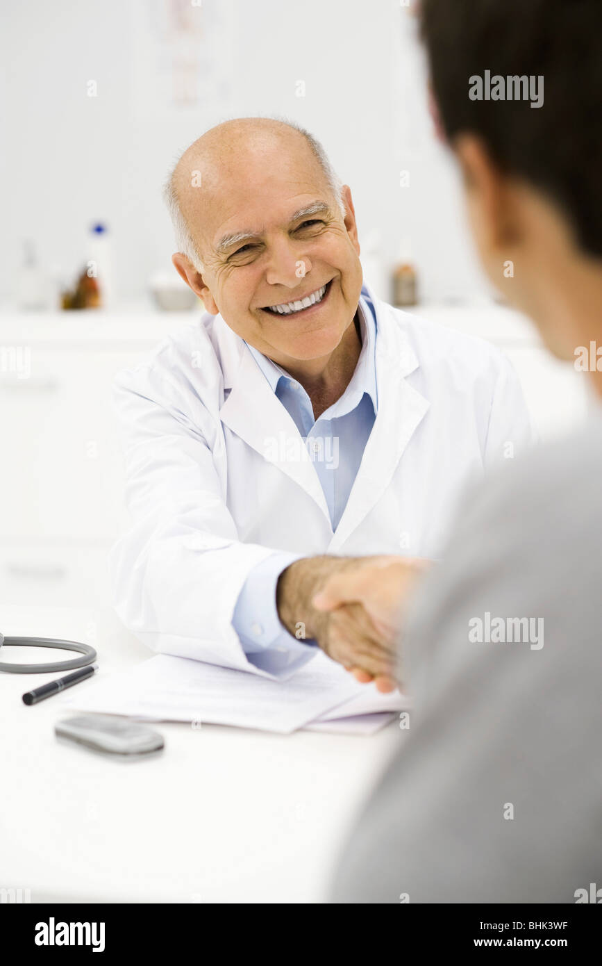 Doctor shaking patient's hand - Stock Image