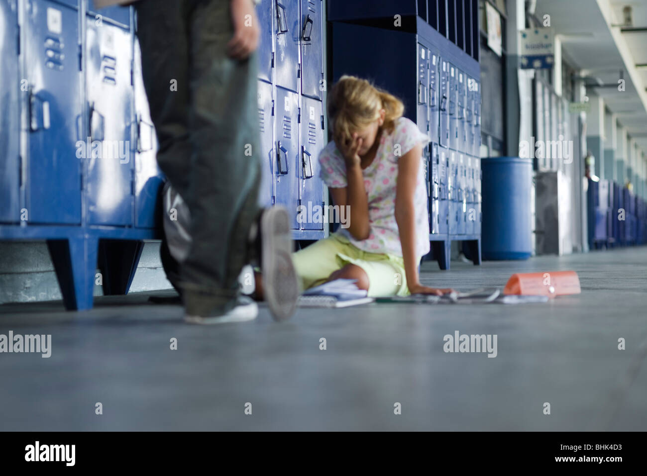 Junior high student sitting on floor crying, boy standing by watching - Stock Image