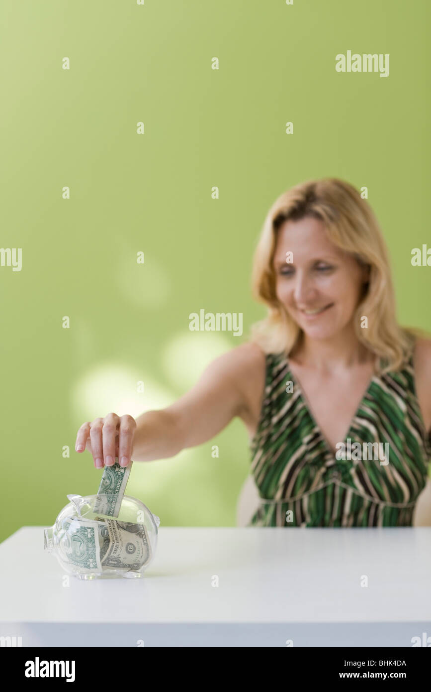 Woman putting dollar bill in piggy bank - Stock Image