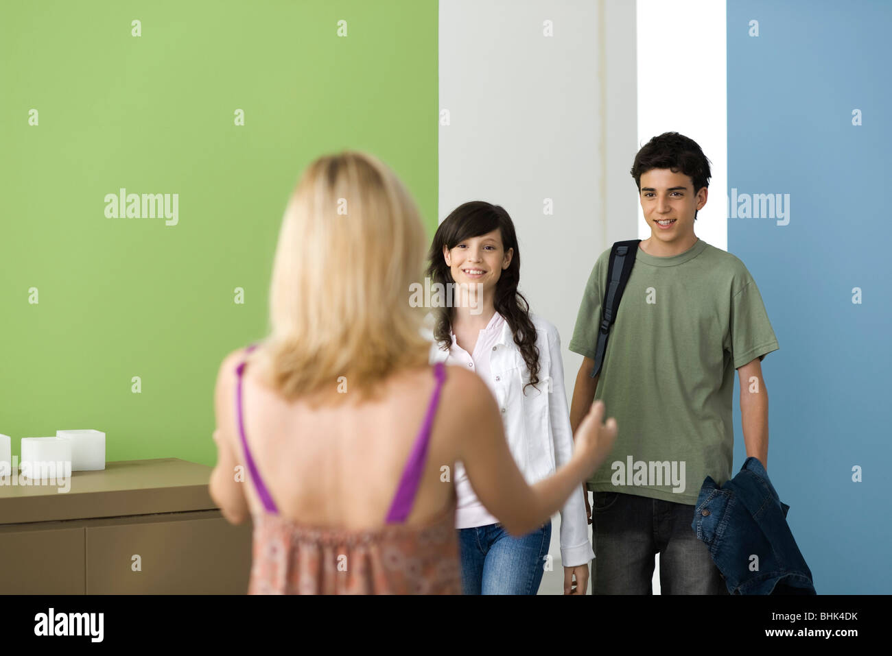 Mother welcoming teenages home - Stock Image