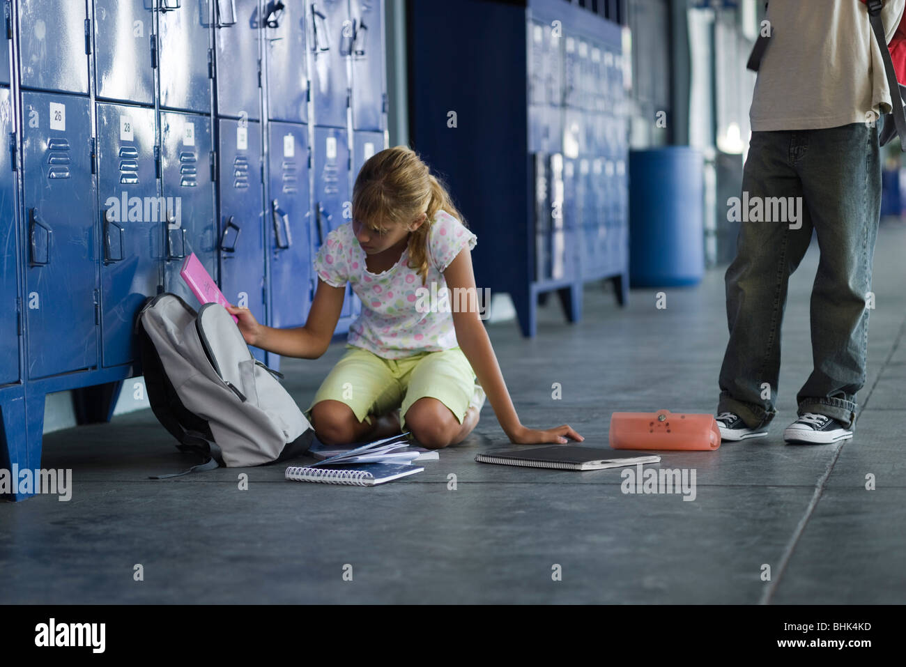 Junior high student picking up dropped school supplies, boy standing by watching - Stock Image