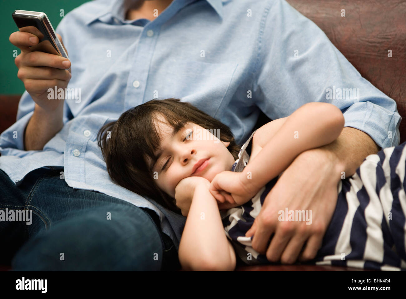 Father text messaging while son naps with head in his lap - Stock Image
