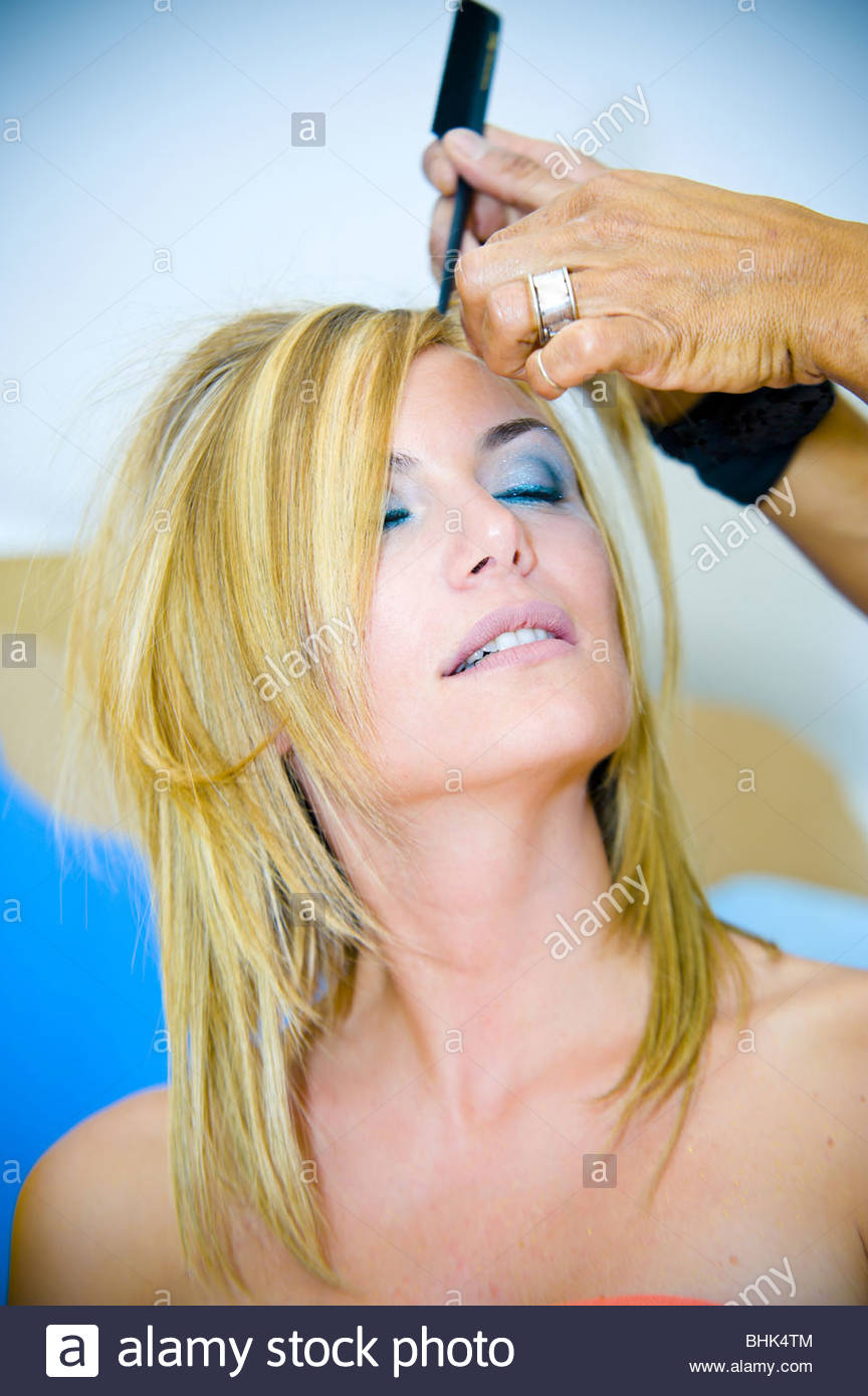 Hair stylist fixing up woman's hair - Stock Image