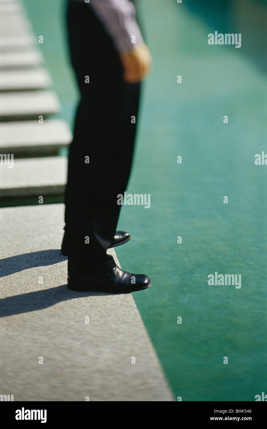 Businessman standing at edge of pool, low section - Stock Image