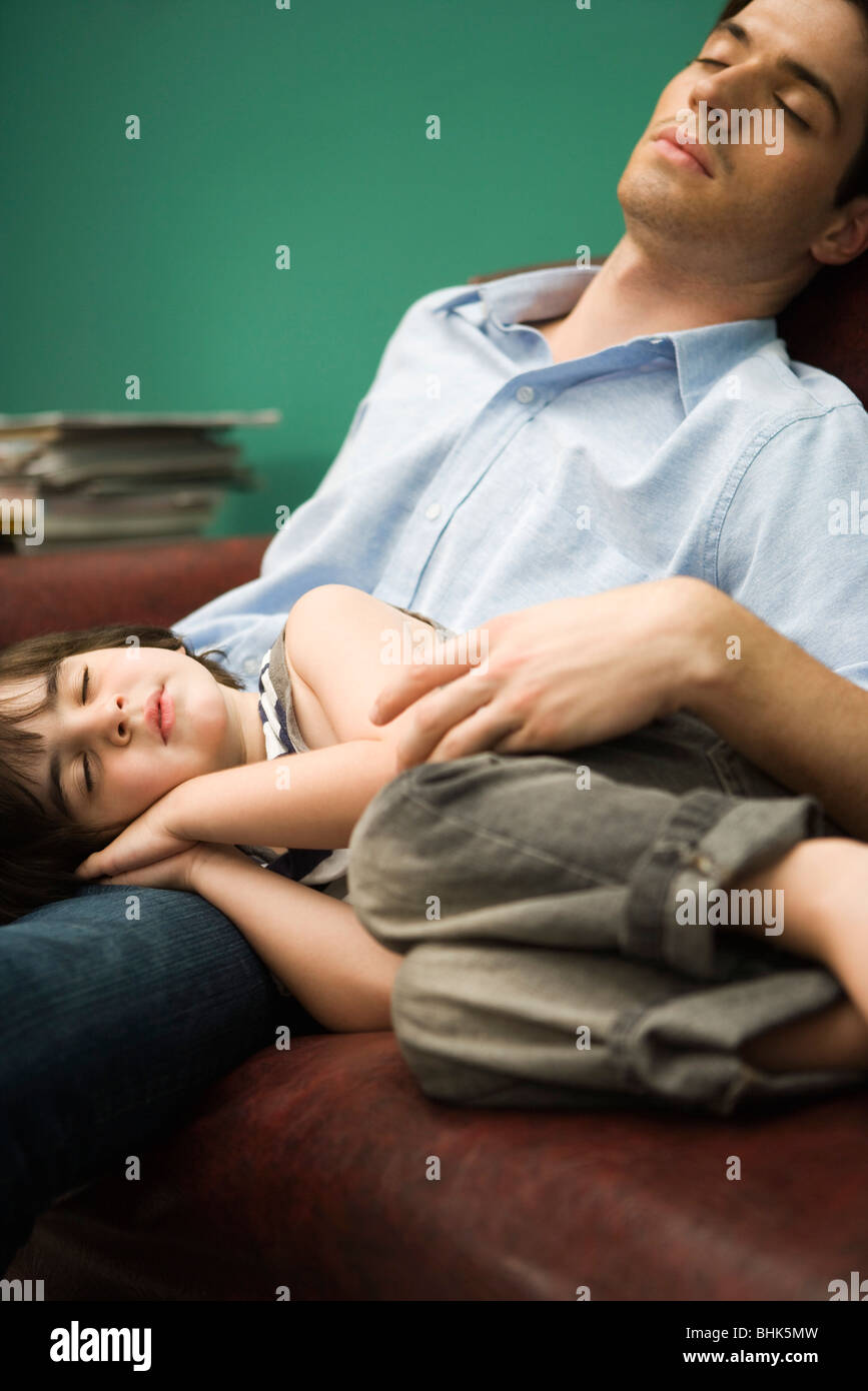 Father and son napping together on sofa - Stock Image