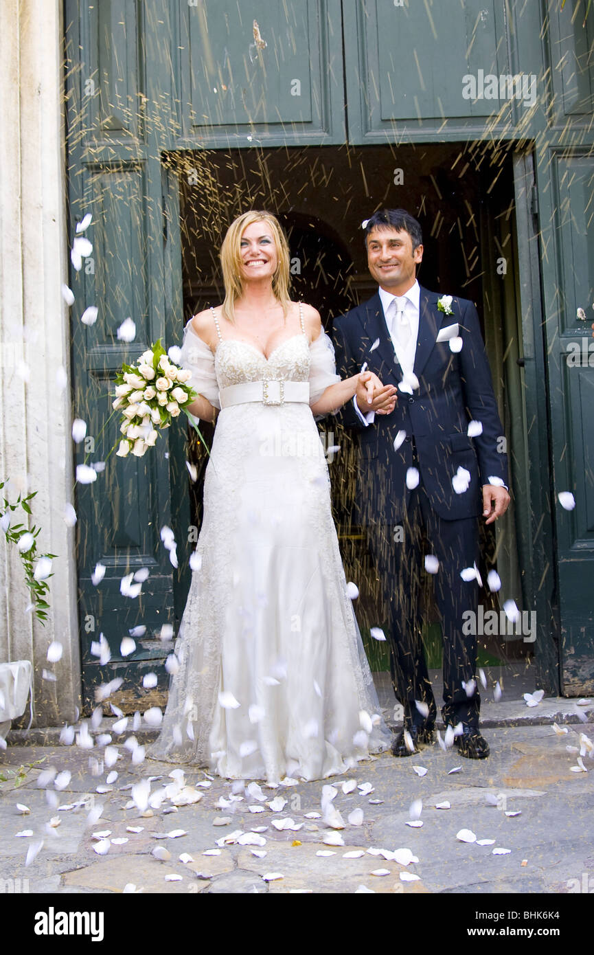 47759813ea43 Newlyweds during rice and petal throwing after wedding ceremony - Stock  Image