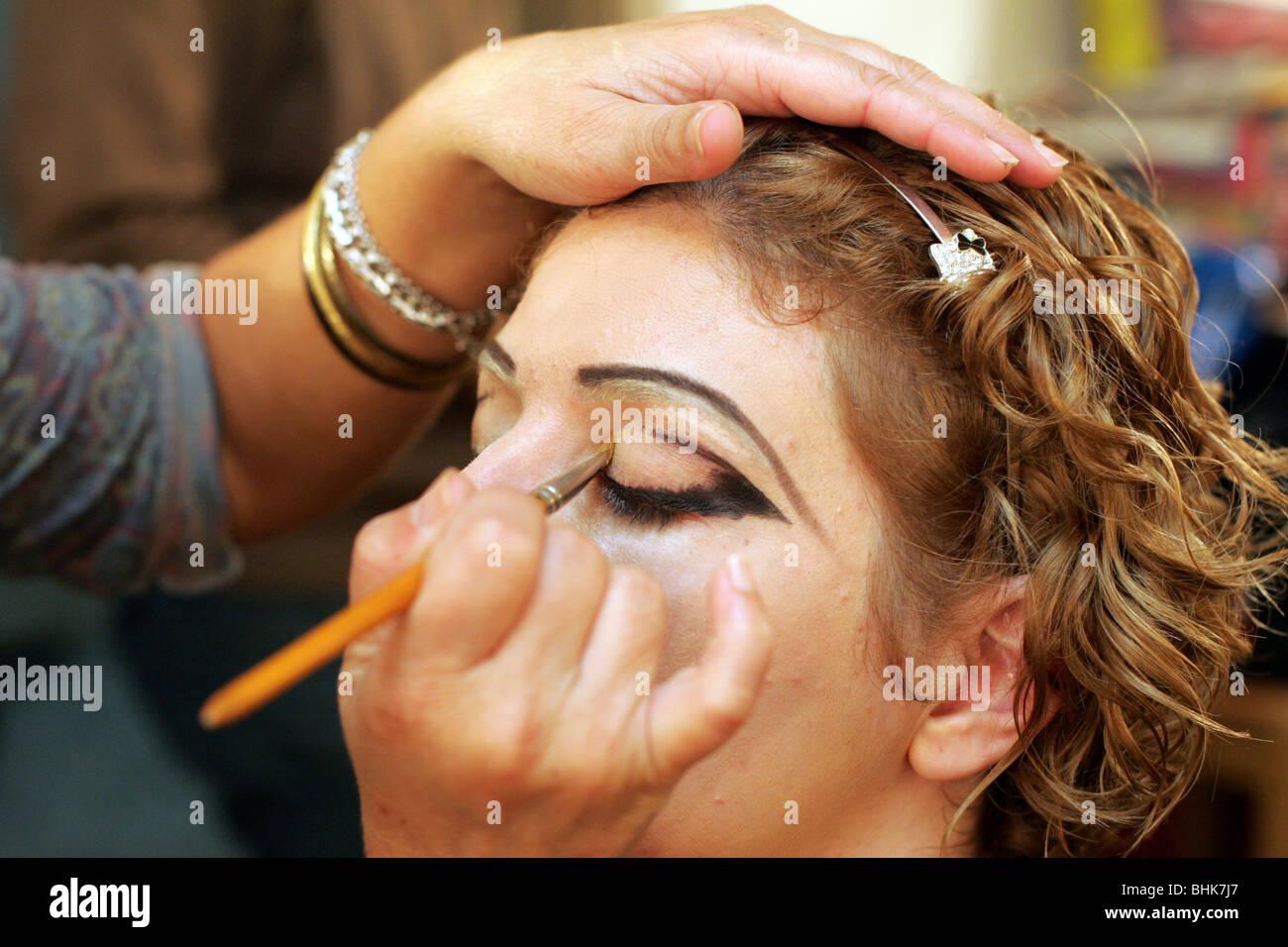 Makeup artist applying eyeliner to an actress. - Stock Image