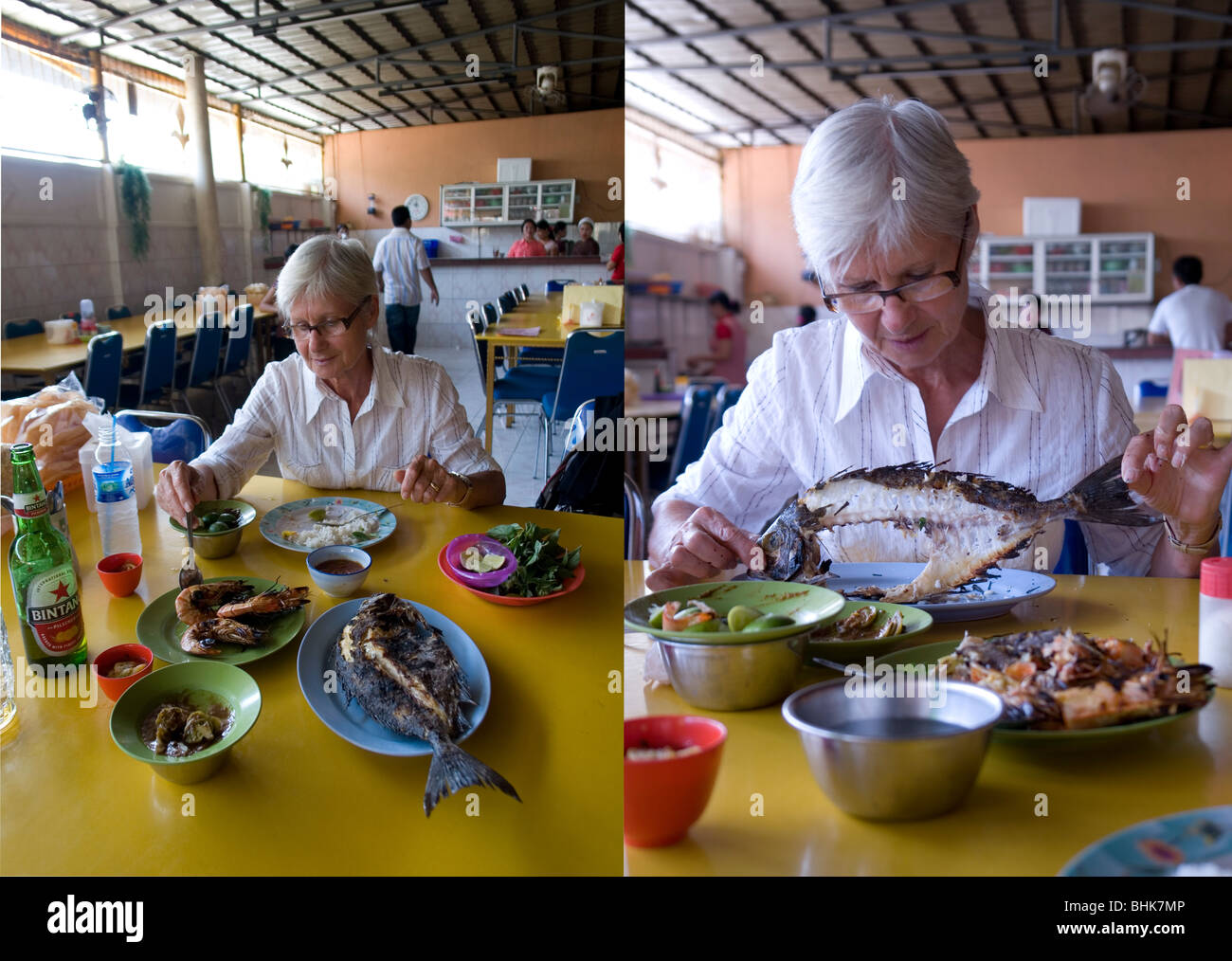 Fish-eating with fingers for an inexperienced senior tourist (Sulawesi). Touriste s'essayant à manger du - Stock Image