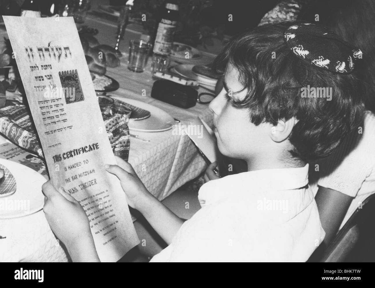 An American boy reading his Bar Mitzvah certificate, Israel, 1971. - Stock Image