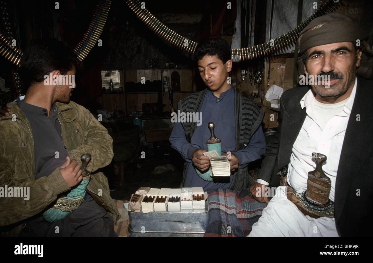 Man counts money in armaments shop in Dhamar, Yemen. - Stock Image