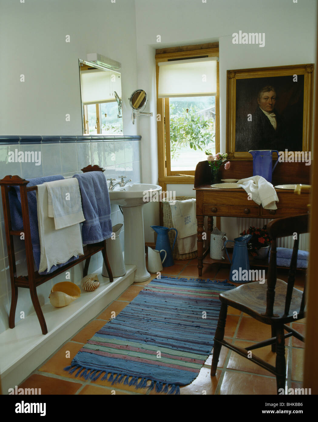 Large oil painting above basins in antique vanity unit in country bathroom  with blue striped cotton rug - Large Oil Painting Above Basins In Antique Vanity Unit In Country