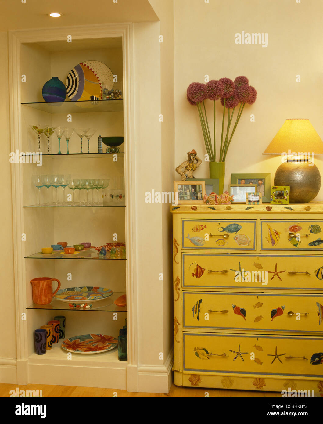 Wineglasses and crockery on glass shelves in alcove beside painted ...