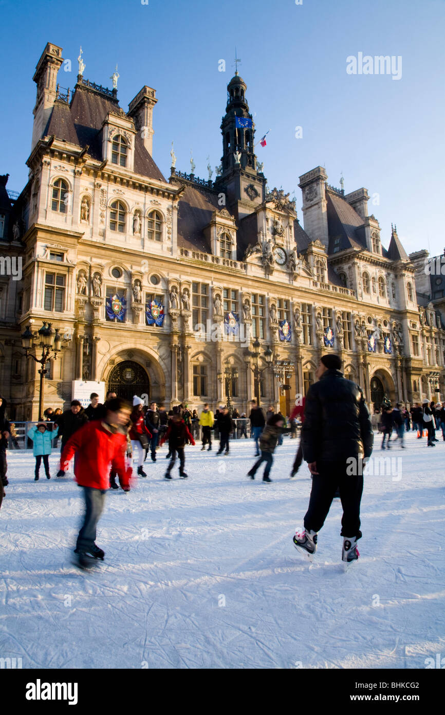 Ice rink and winter ice skaters in front of the Hôtel de Ville / City Hall in Paris, France. Stock Photo