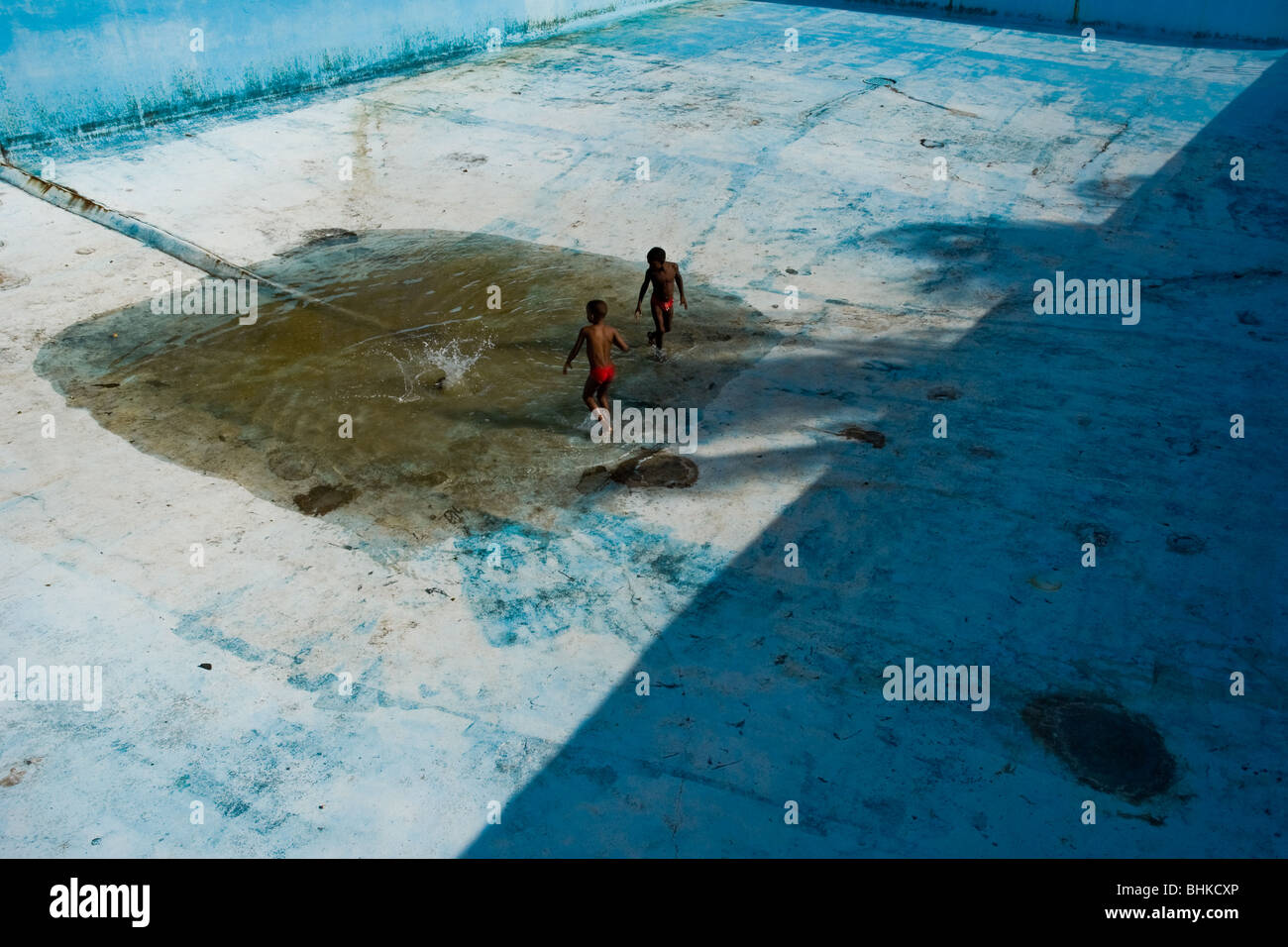 Cuban kids playing a game in the bottom of the old drained swimming pool in a small costal village of Siboney, Cuba. - Stock Image