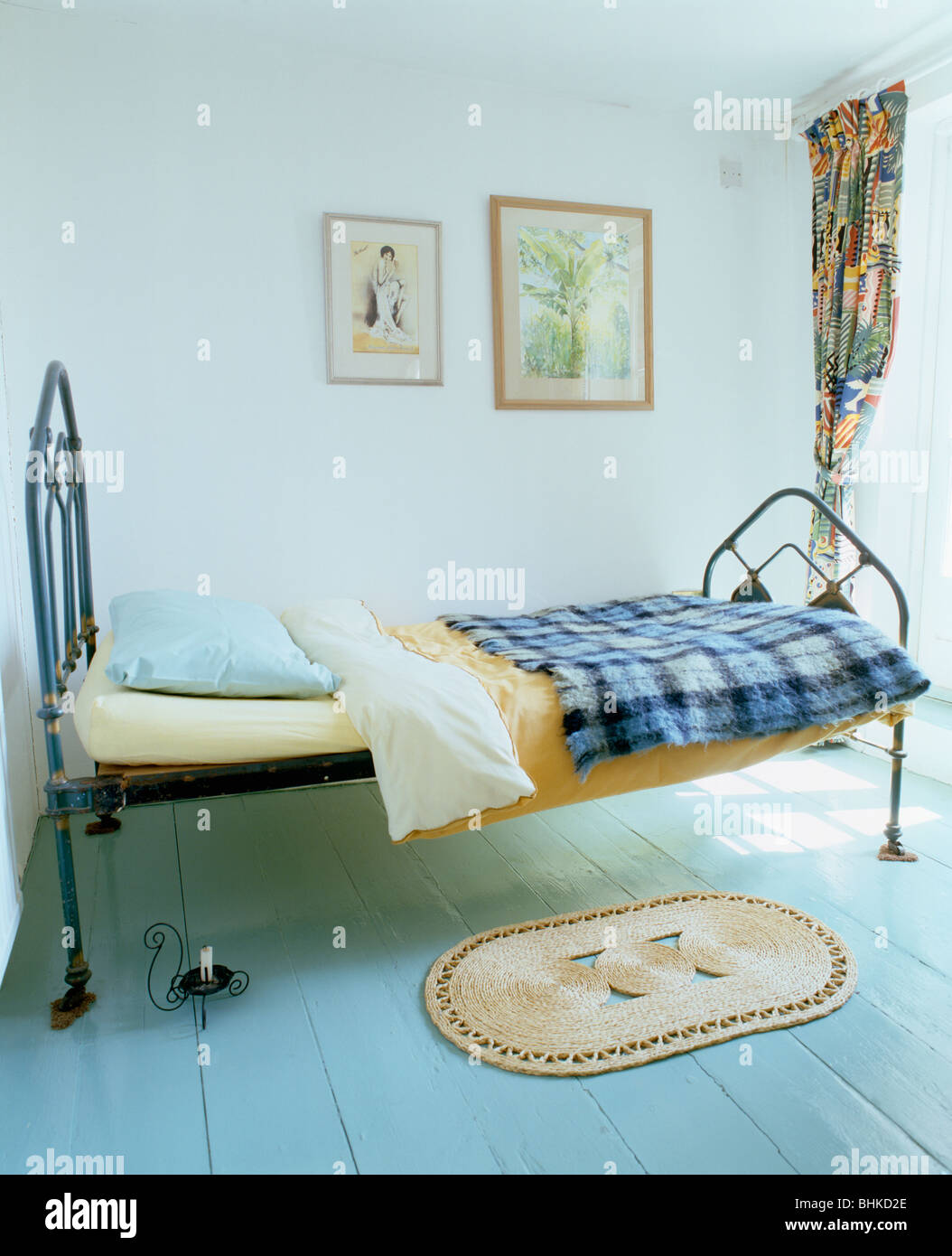 Blue Checked Blanket On Black Cast Iron Single Bed In Simple White Bedroom With Small Rug Pale Painted Wooden Floor
