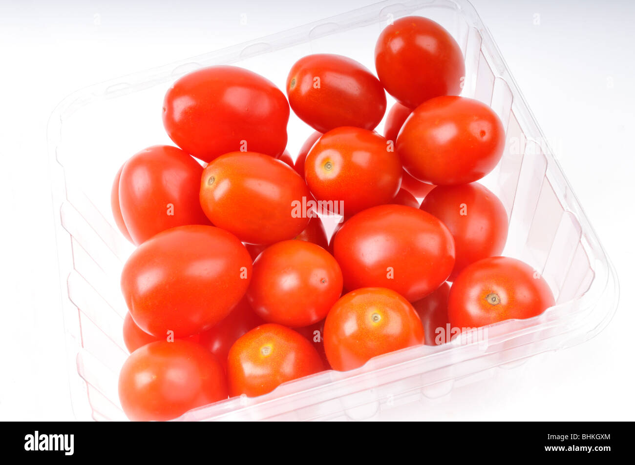 Red cherry tomatoes in clear plastic container on white background - Stock Image