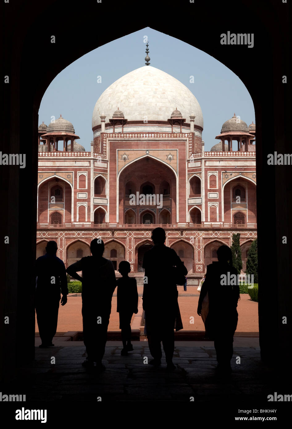 India Haryana New Delhi Visitor's silhouetted under the entrance portal to Humayun's tomb - Stock Image