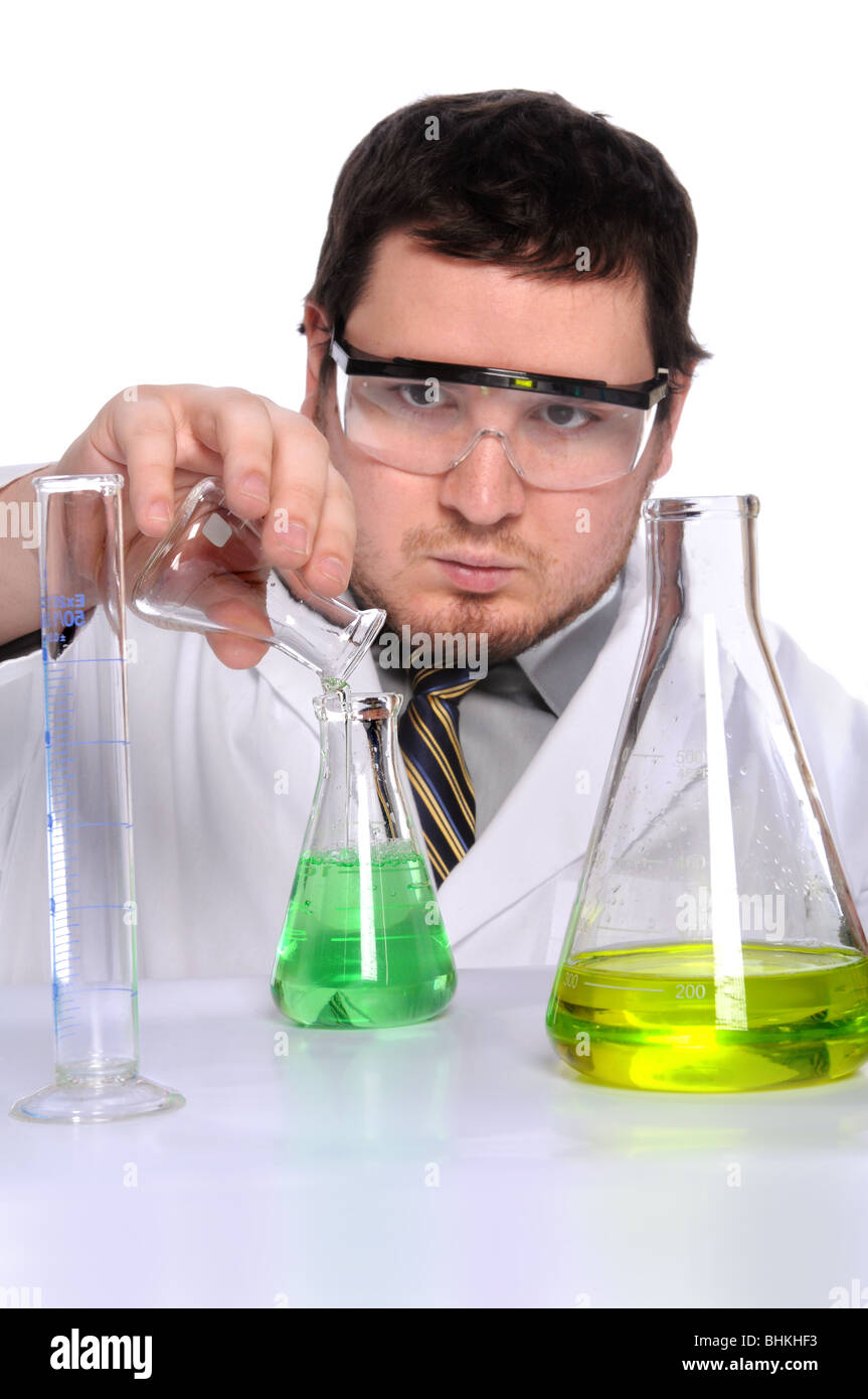 Scientist working in laboratory pouring liquid into flask - Stock Image