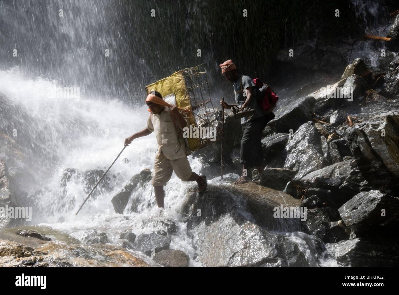 Porters carrying loads across waterfall, near Karte, Annapurna Circuit, Nepal - Stock Image