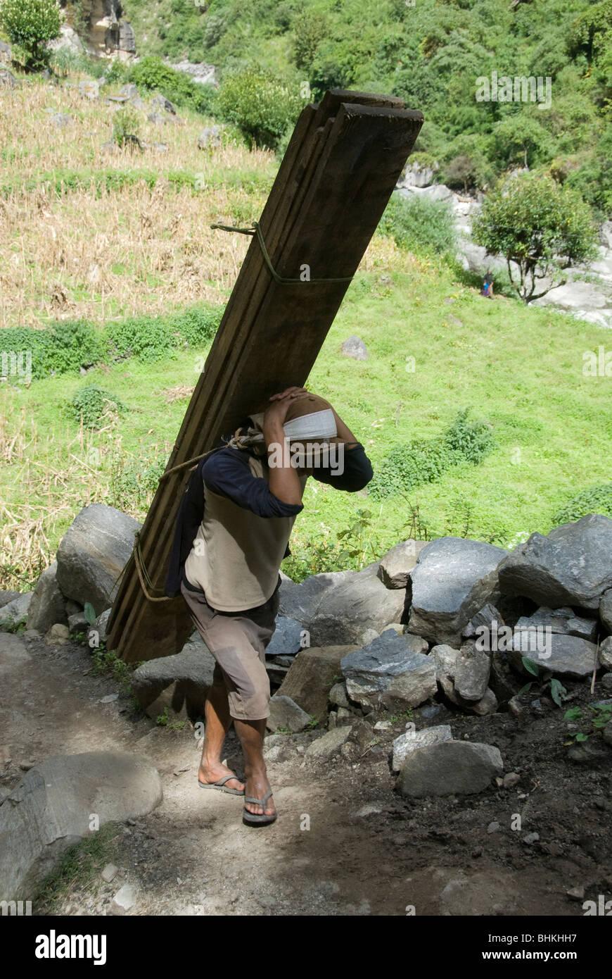 Porter carrying heavy loads, Annapurna Circuit, Karte, Nepal - Stock Image
