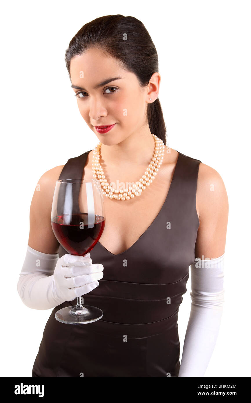 A beautiful woman in a classy dress is holding a glass of red wine. - Stock Image