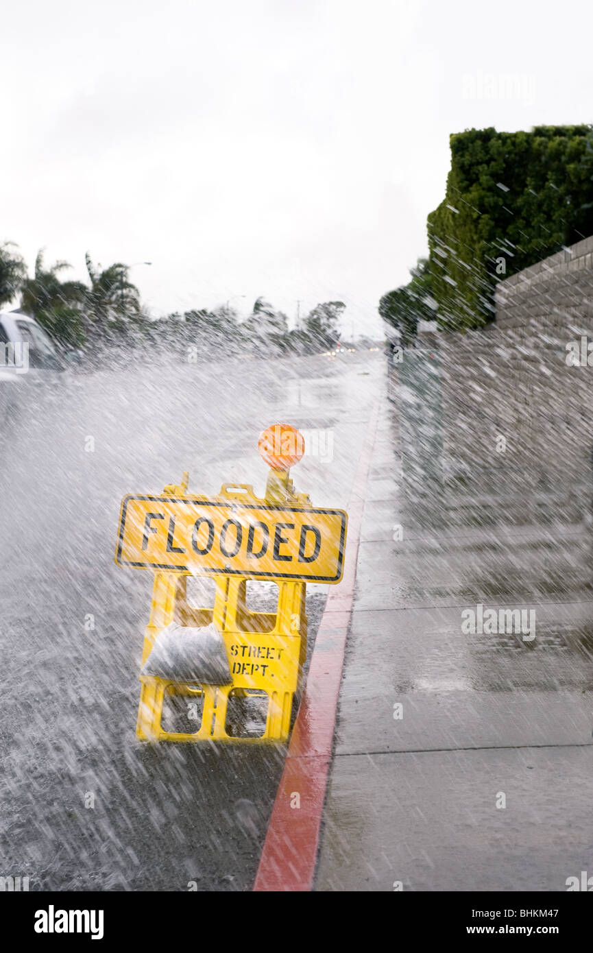 A car kicks up a pool of rainwater over a street flooded sign during bad, rainy weather. - Stock Image
