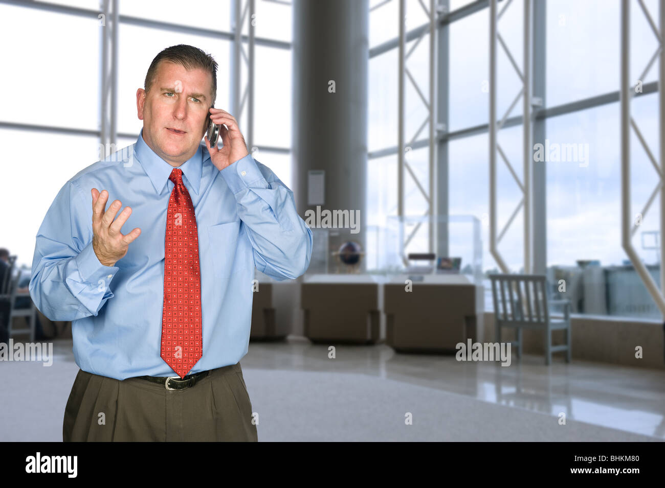 A businessman talking on his cell phone is not happy with the tone of the conversation. - Stock Image