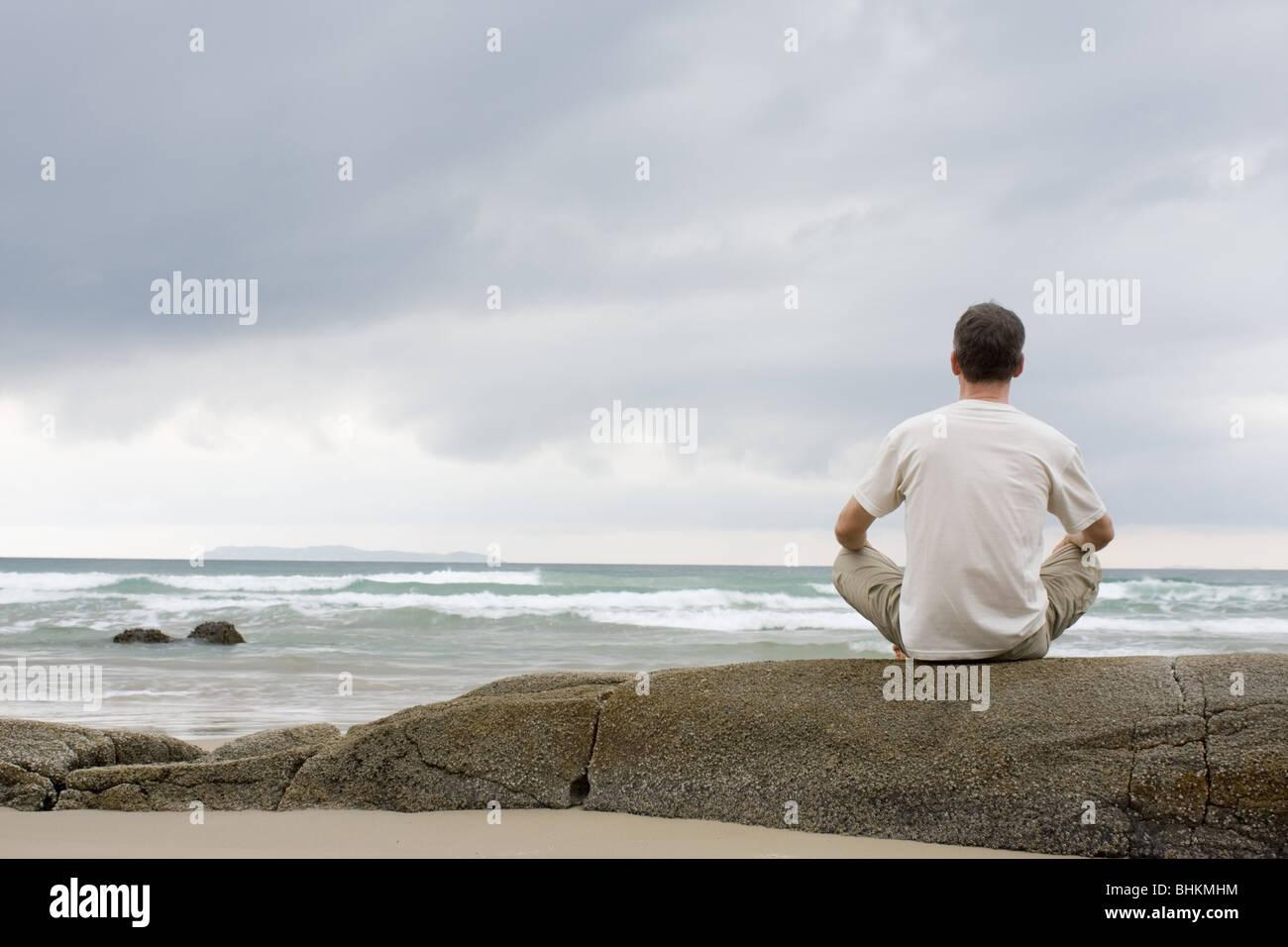 Man meditating on a rock at the sea - Stock Image
