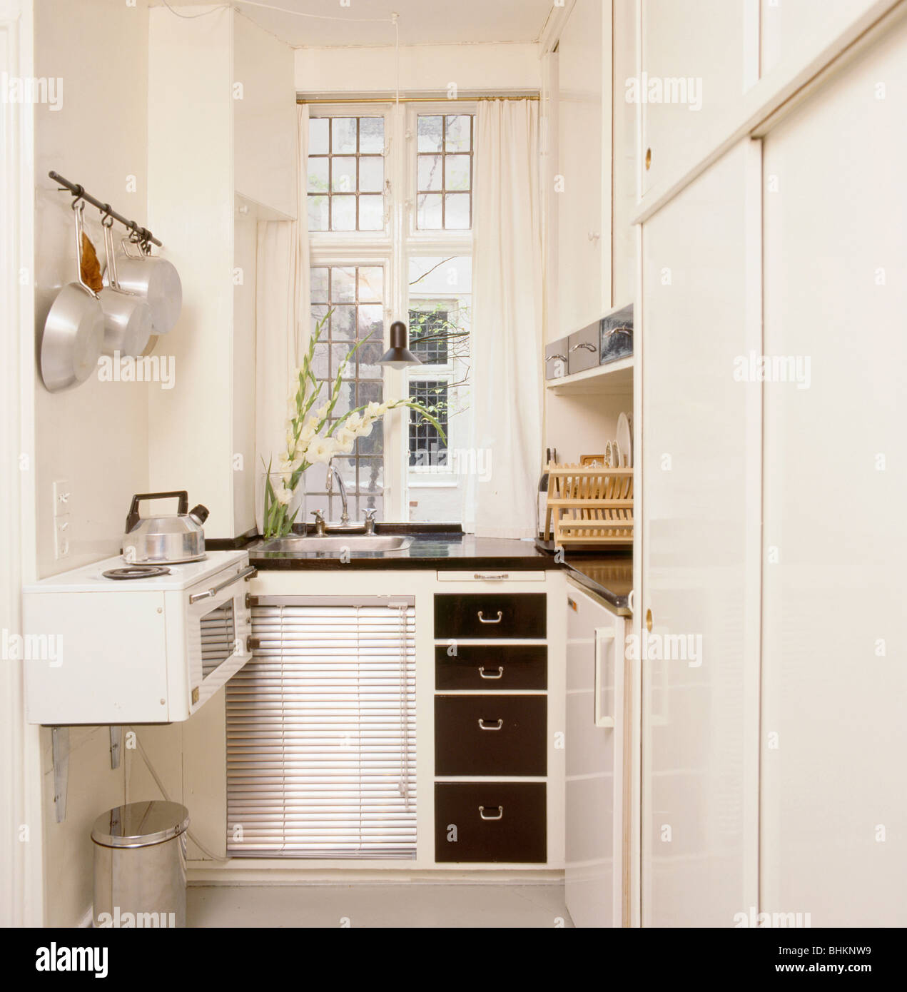 Kettle on hob of small wall-mounted oven in compact white kitchen ...