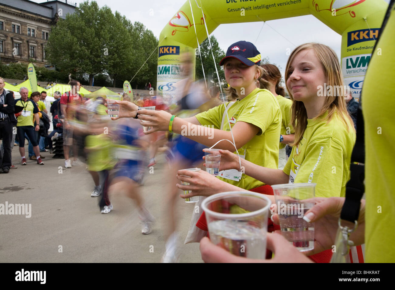 Two girls helping with water glasses for runners. Marathon in Dresden, Germany - Stock Image