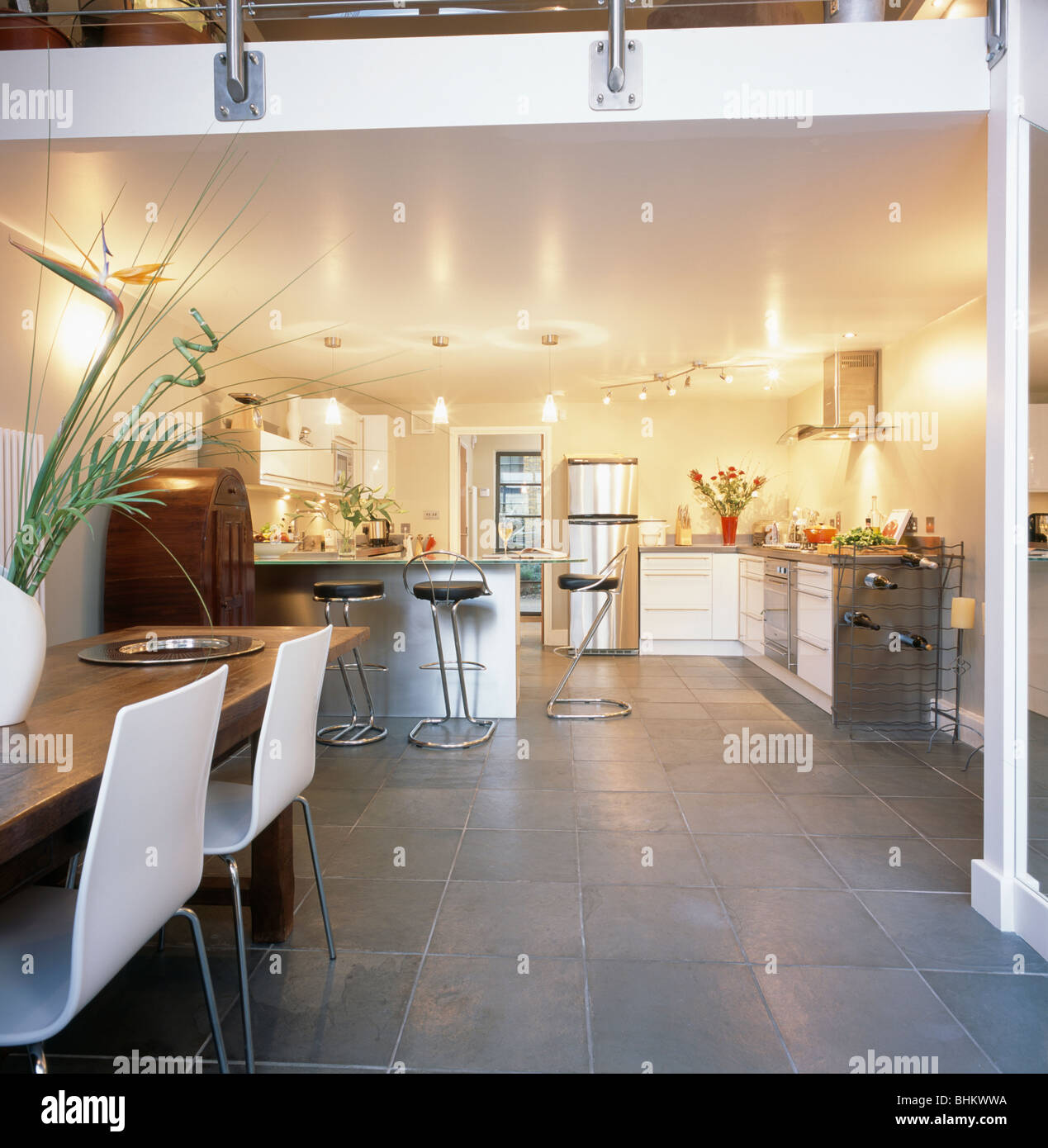 Slate flooring in modern open plan dining room and kitchen in city ...