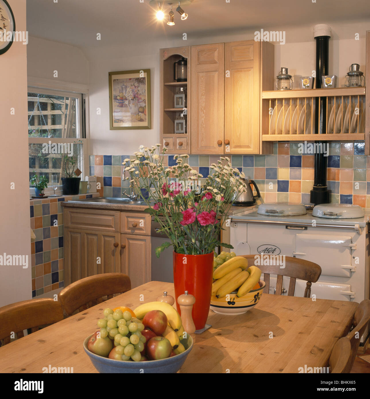 kitchen ceiling spot lighting. flowers in red vase on pine table with bowls of fruit country kitchen cream aga oven and ceiling spot-lights spot lighting