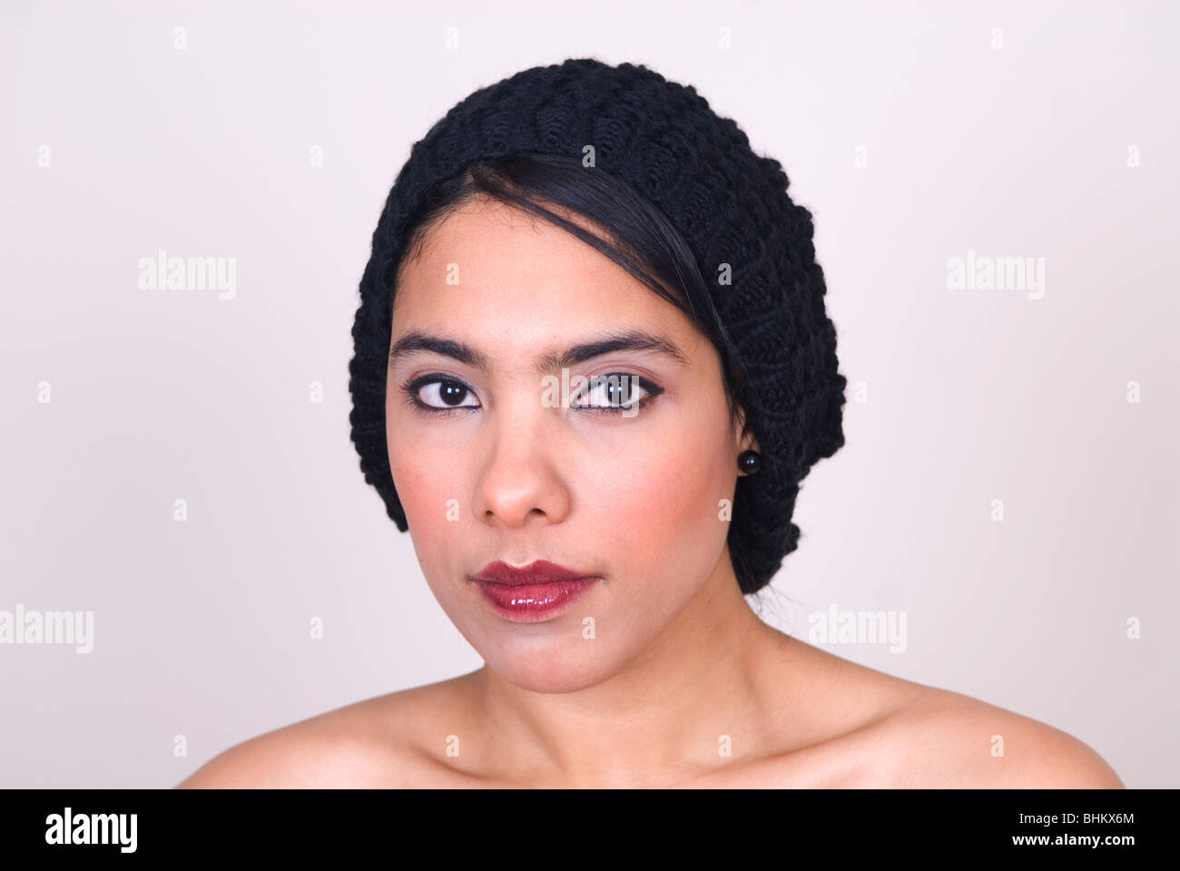Beautiful ethnic woman wearing a woolen hat looking at camera - Stock Image