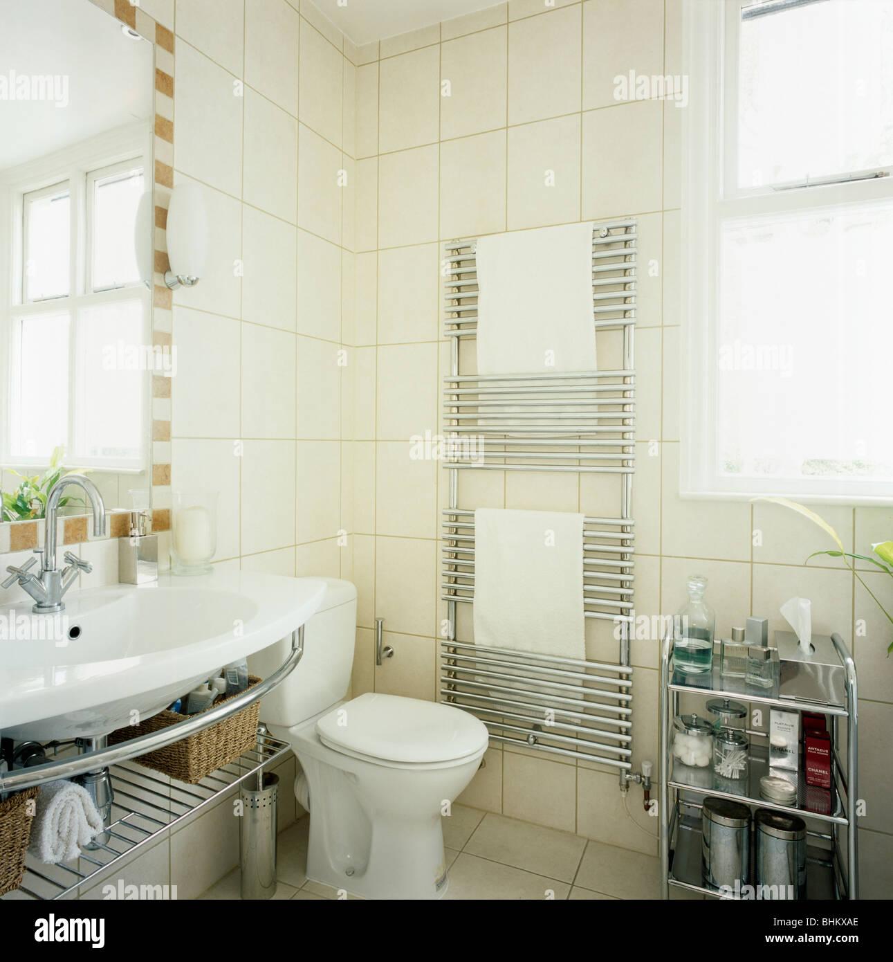 Vertical stainless steel radiator in modern white tiled bathroom ...