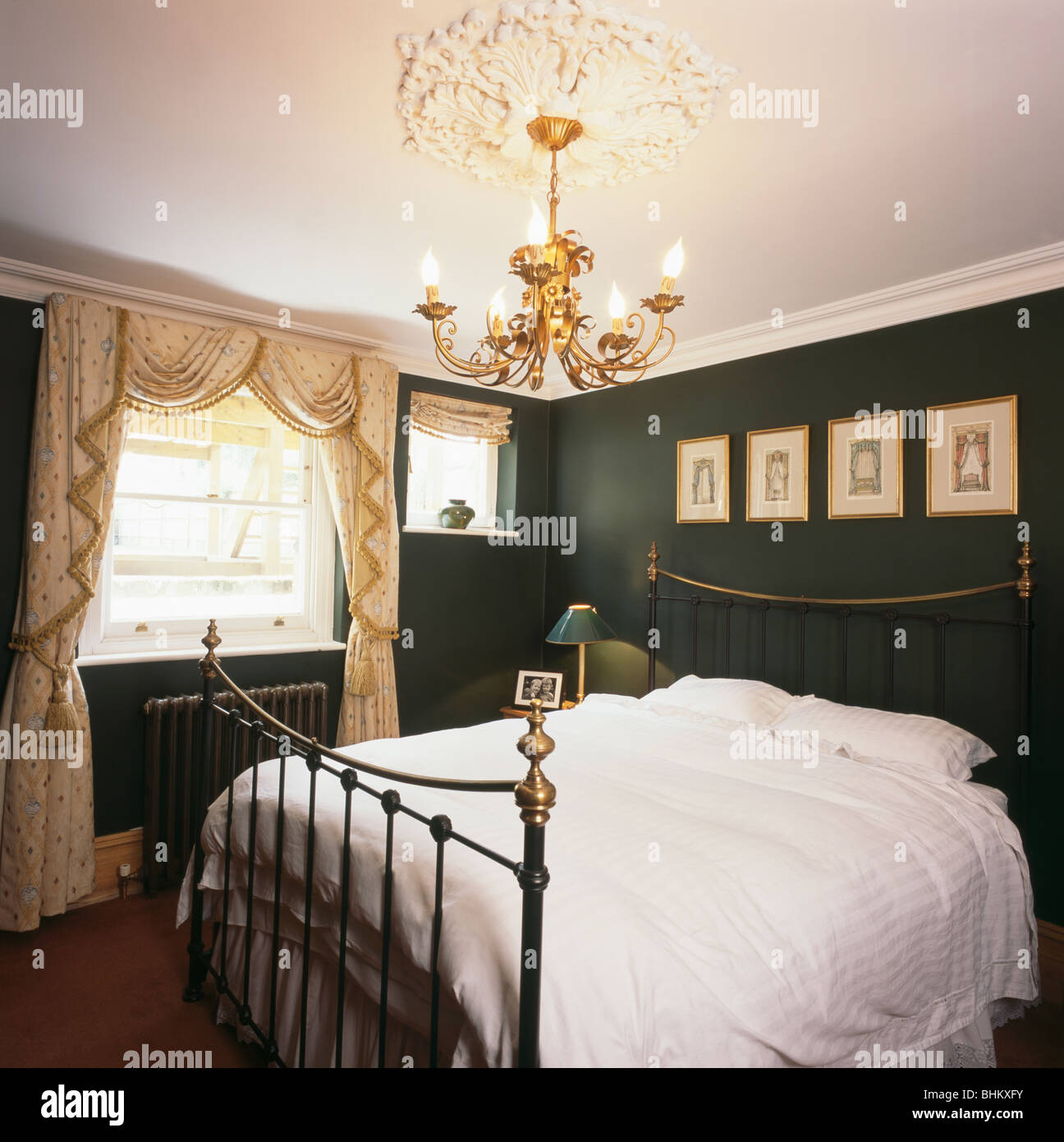 Gilt chandelier above antique brass bed in green and white bedroom ...