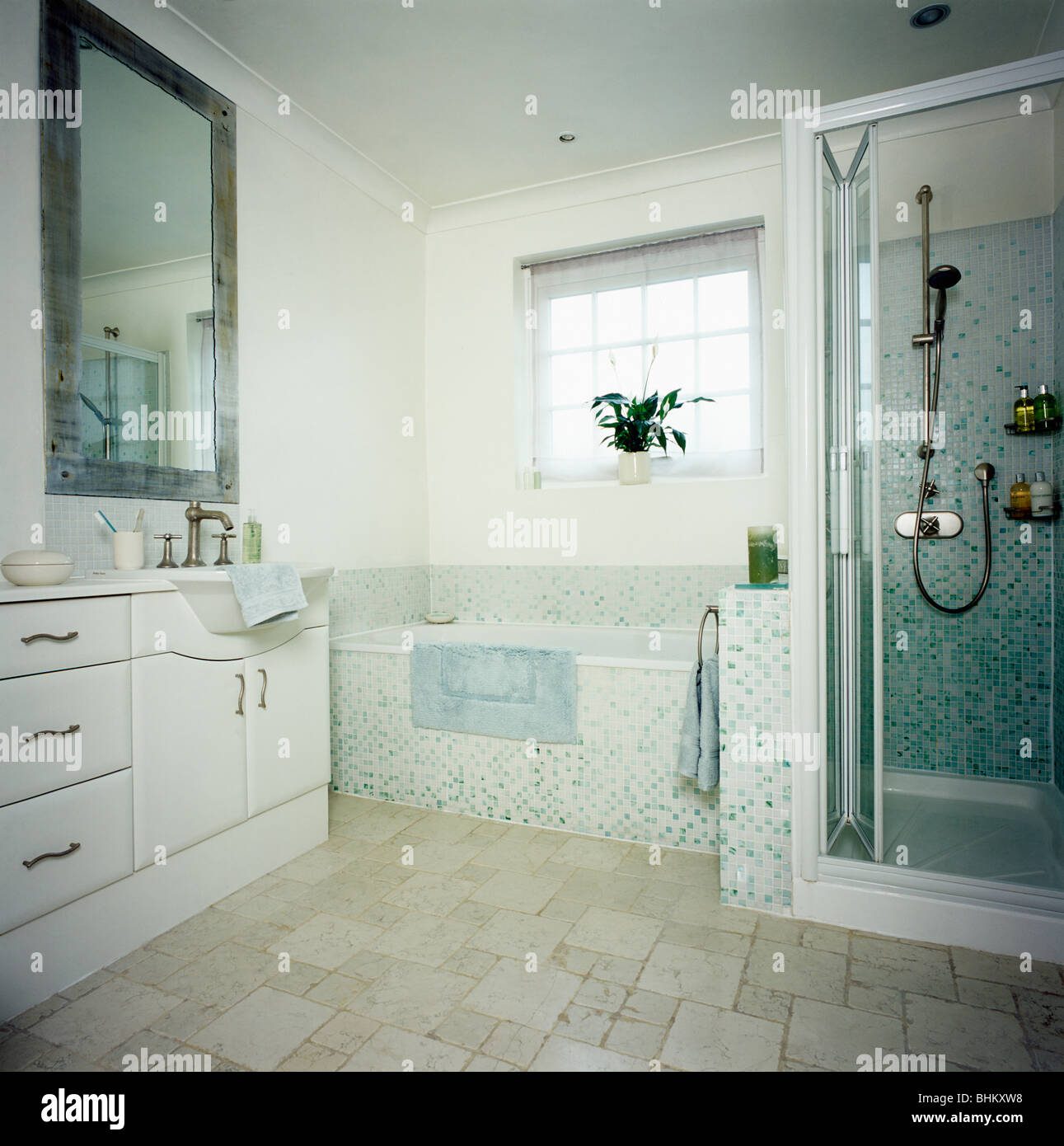 Mosaic tiled bath in modern white bathroom with shower cabinet and ...