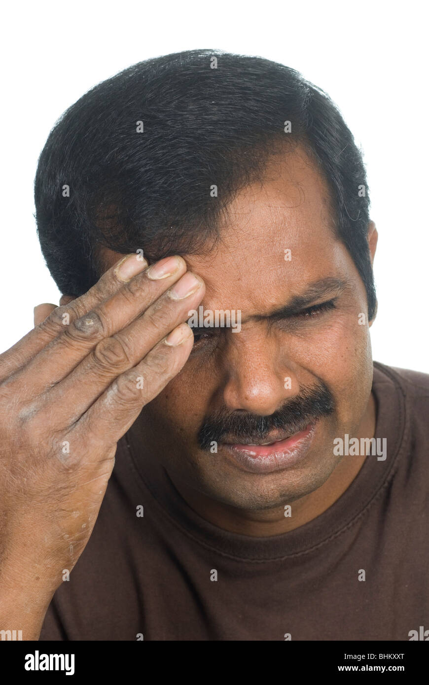 Indian man with a headache against a white background - Stock Image