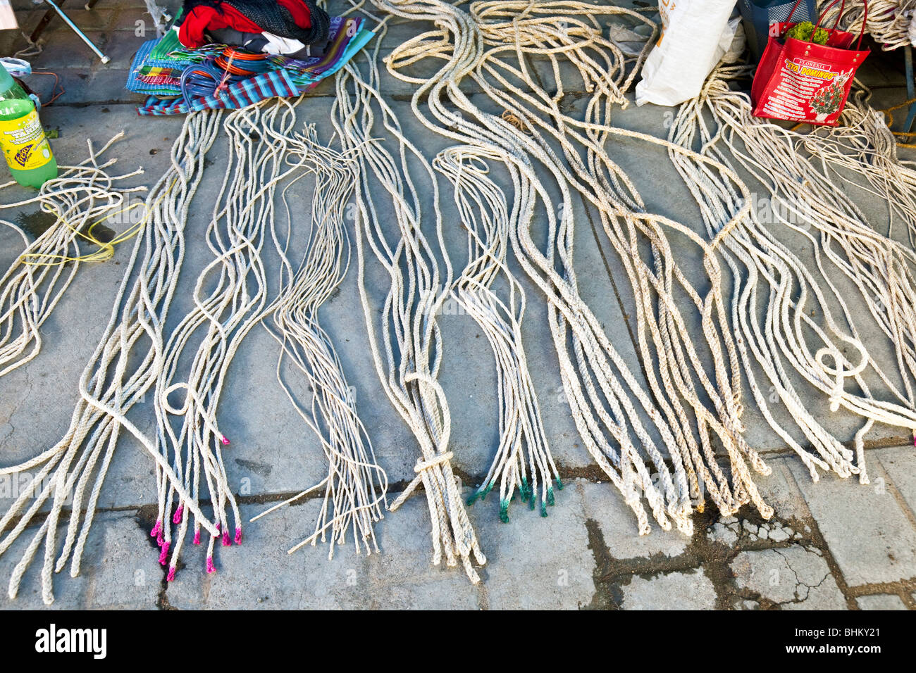 lengths of hemp rope of varying thickness laid out on paving stones for sale at Ocotlan market Oaxaca Mexico - Stock Image