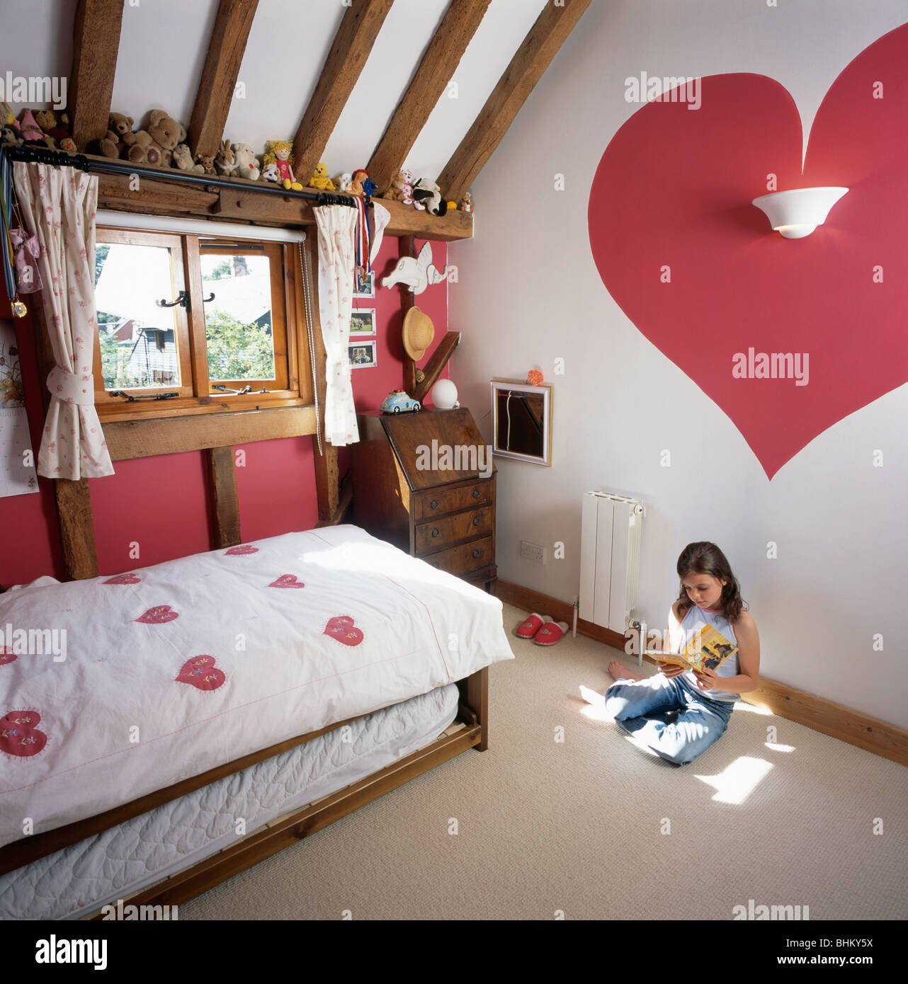Small girl in child\'s country cottage bedroom with red heart ...