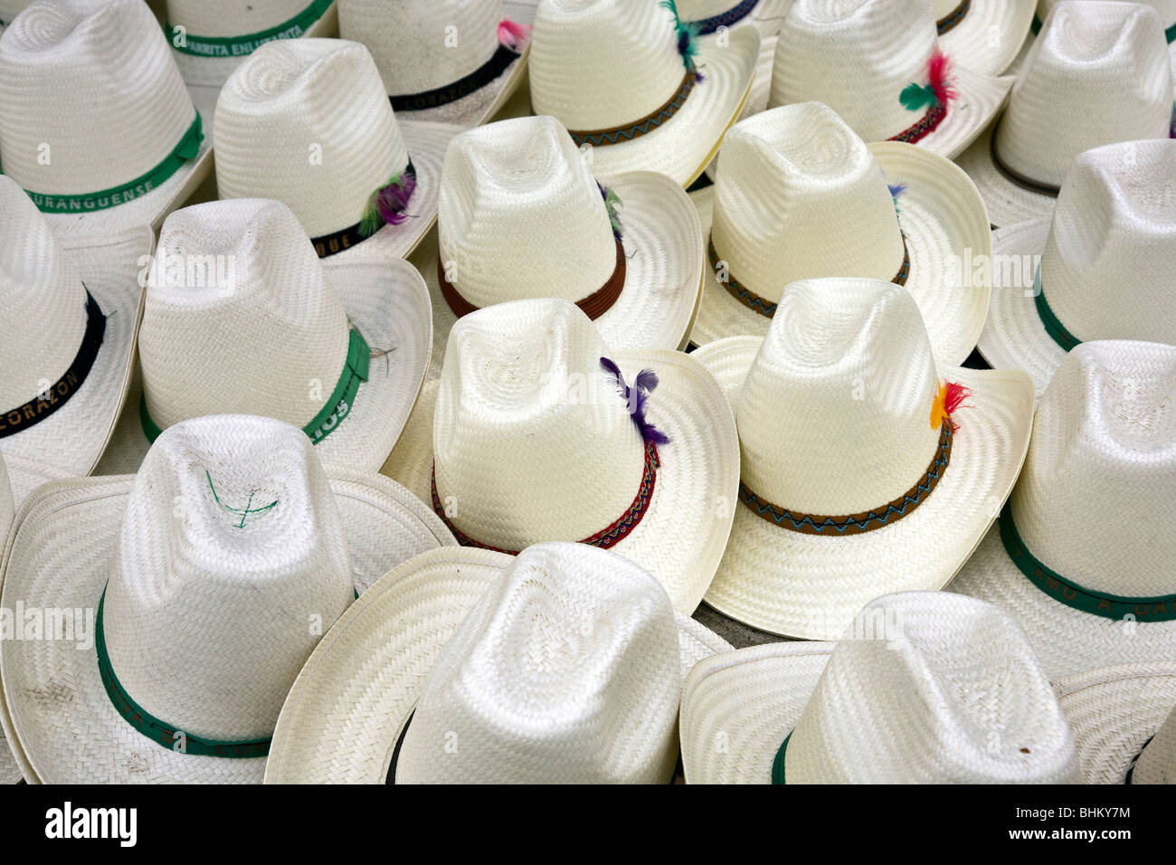 e9d2057828449 white straw sombreros with pretty feathers in their colored bands spread  out for sale at Ocotlan