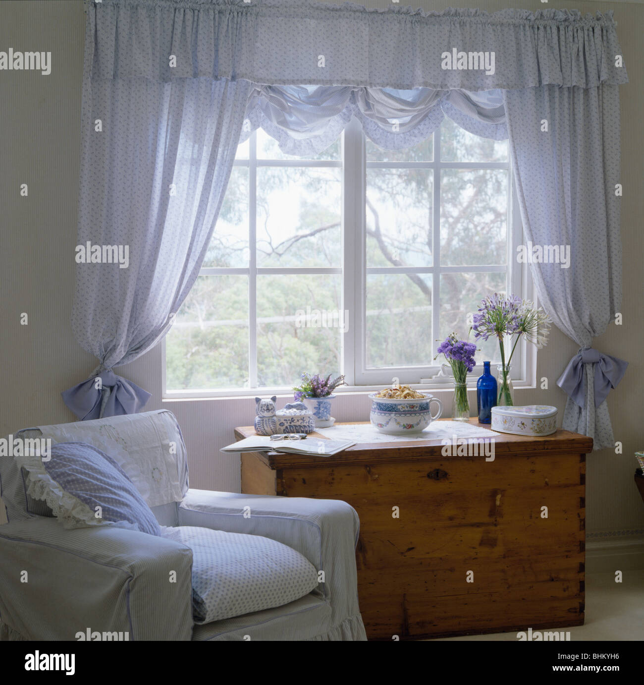 White Armchair And Pine Chest Of Drawers Below Window With Pale Blue Voile  Curtains In Country Bedroom