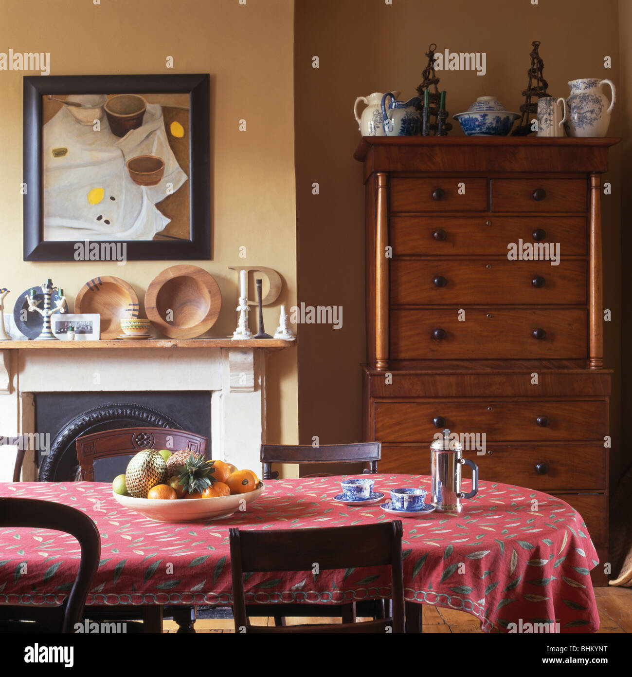 Pink Patterned Cloth On Table In Small Dining Room With Tall Antique Chest  Of Drawers Beside Fireplace