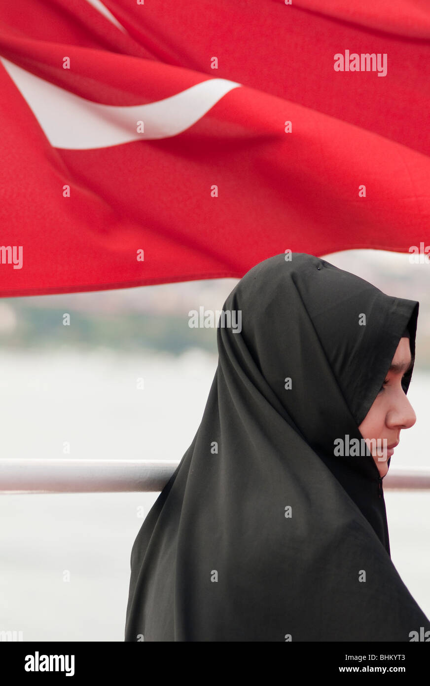 A young women wearing a hijab stands in front of the Turkish national flag - Stock Image