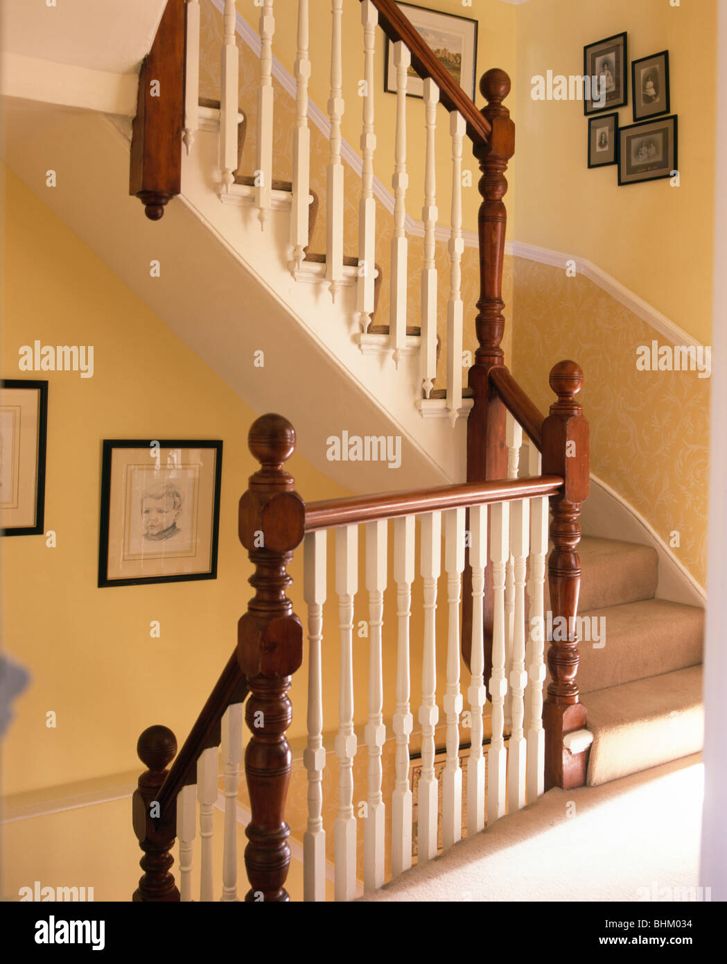 Mahogany Newel Posts And Cream Banisters On Staircase On Traditional Yellow  Landing   Stock Image