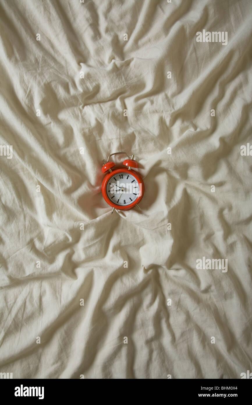 Red alarm clock centered on a wrinkled duvet - Stock Image